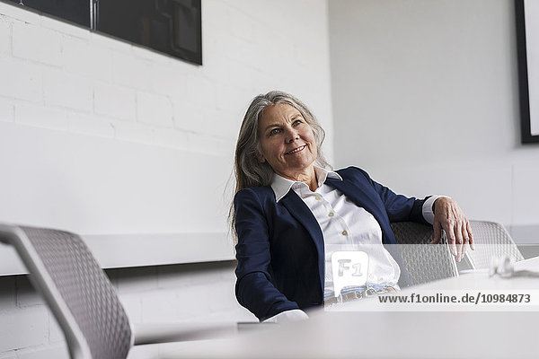 Smiling senior businessswoman sitting at conference table
