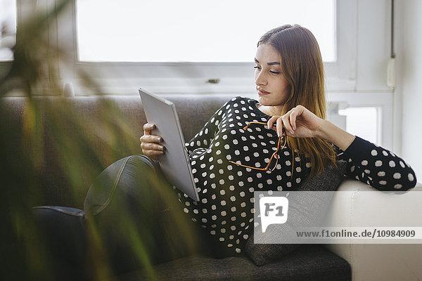 Junge Frau entspannt auf der Couch mit ihrer Tablette