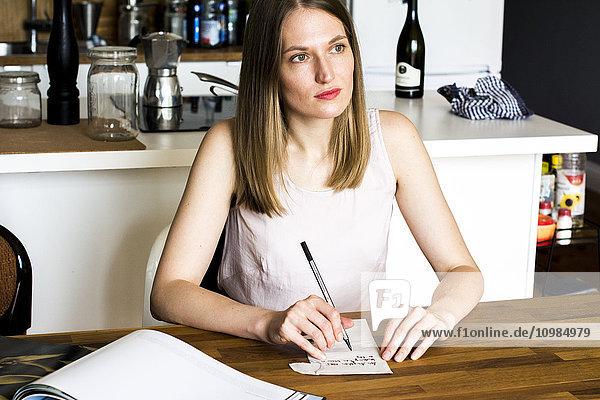 Nachdenkliche Frau  die in ihrer Küche am Tisch sitzt und Notizen macht.
