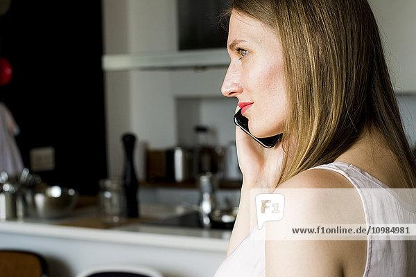 Frau telefoniert mit Smartphone zu Hause