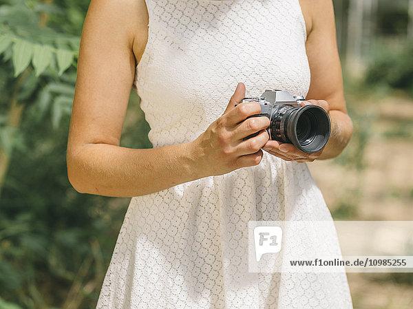 Junge Frau in weißem Kleid mit Kamera