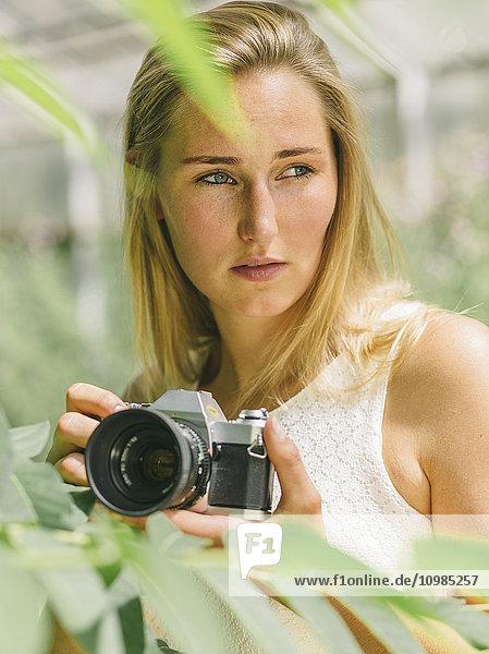 Junge Frau hinter der Pflanze mit Kamera