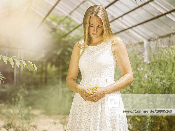 Blonde junge Frau in weißem Kleid steht im Gewächshaus und hält Blumen.
