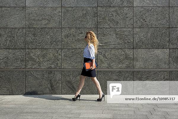 Geschäftsfrau mit Buch und digitalem Tablett im Außenbereich
