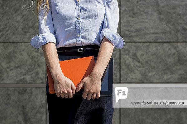 Geschäftsfrau mit Buch und digitalem Tablett im Freien