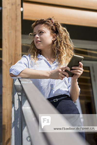 Businesswoman holding cell phone outdoors