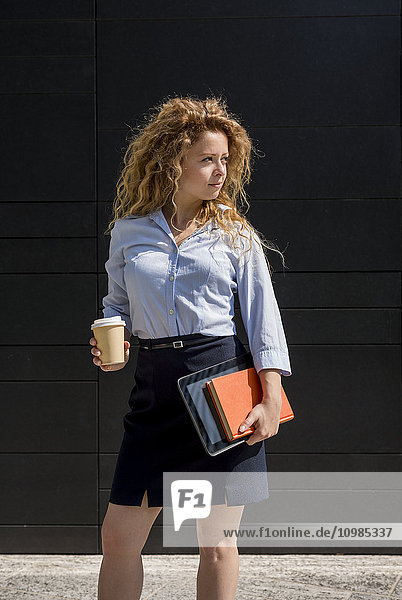 Businesswoman holding coffee to go  book and digital tablet outdoors
