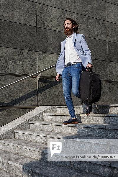 Stilvoller Geschäftsmann mit Koffer auf der Treppe im Freien