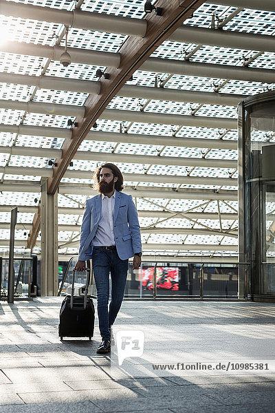 Stilvoller Geschäftsmann beim Gehen mit Koffer