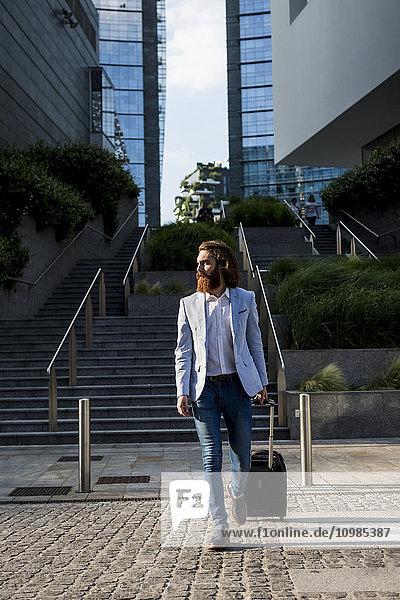 Stilvoller Geschäftsmann beim Spaziergang mit Koffer im Freien