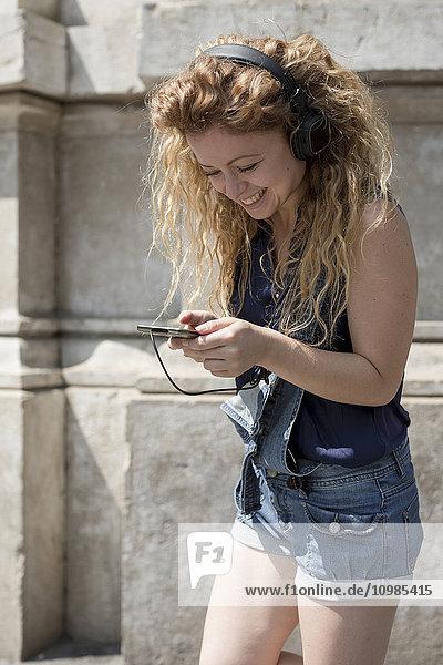Lächelnde junge Frau mit Kopfhörer-SMS
