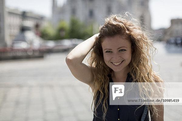 Italien  Mailand  Porträt der lächelnden jungen Frau mit der Hand im Haar