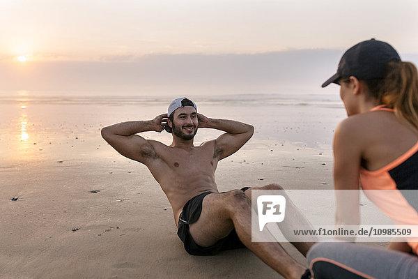 Sportlerpaar beim Training am Strand bei Sonnenuntergang