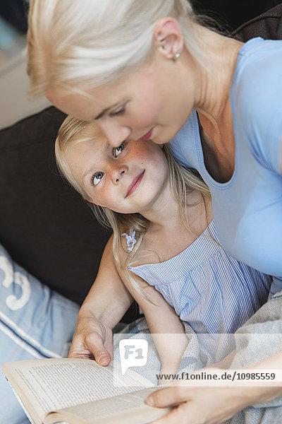 Mutter und kleine Tochter sitzen zusammen auf der Couch mit einem Buch