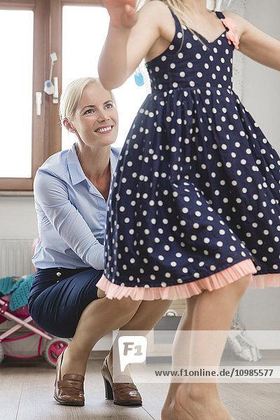 Geschäftsfrau  die ihre kleine Tochter beim Tanzen im Kinderzimmer beobachtet.