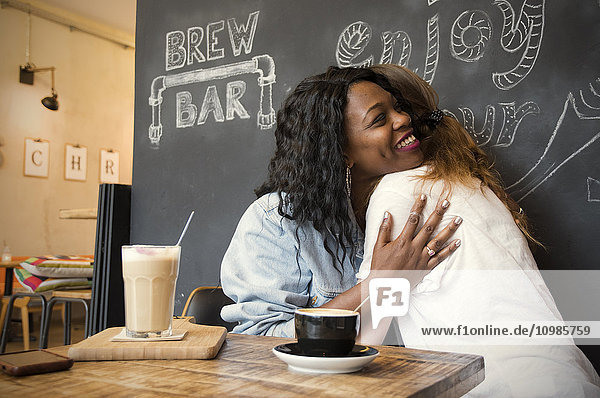 Two friends meeting in cafe  embracing