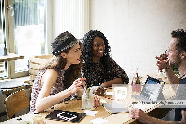 Jugendliche treffen sich im Cafe  diskutieren und nutzen digitale Tabletts