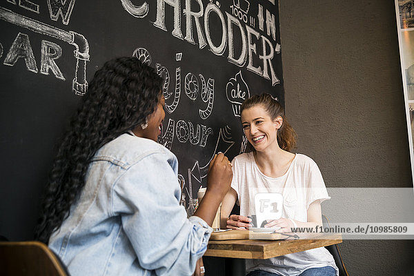Zwei Freunde treffen sich im Cafe  plaudern.