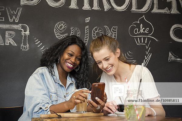 Zwei Freunde im Café beim Blick auf das Smartphone