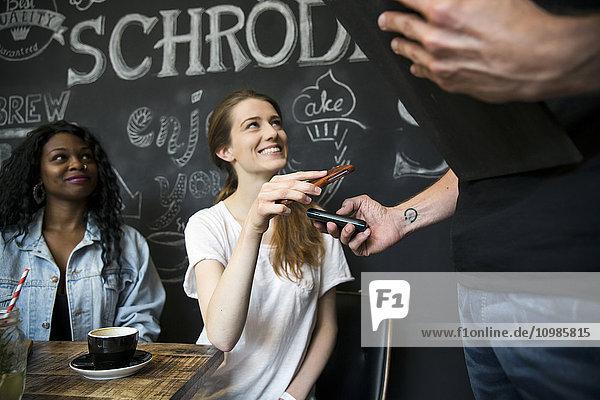 Freunde im Café zahlen mit Smartphone