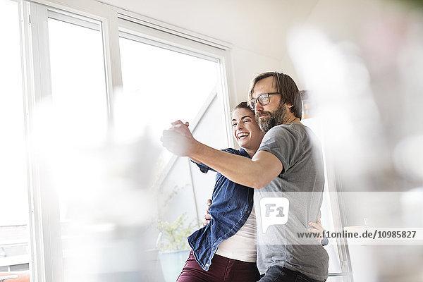Verspieltes Paar tanzt zu Hause
