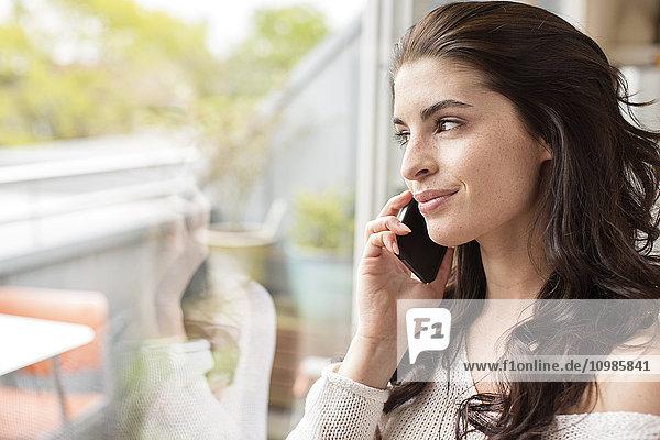 Lächelnde junge Frau am Handy mit Blick aus dem Fenster