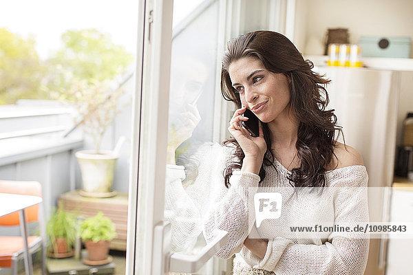 Lächelnde junge Frau am Handy am Fenster