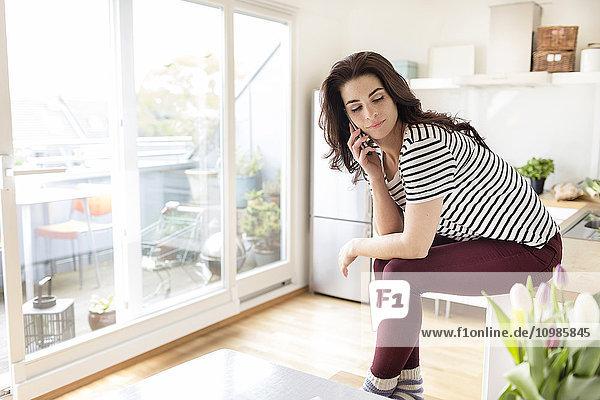 Junge Frau am Handy in der Küche