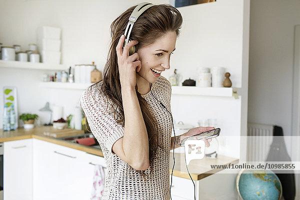 Fröhliche junge Frau in der Küche beim Musikhören