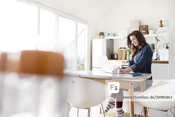 Lächelnde junge Frau zu Hause mit Handy-Laptop