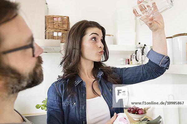 Skeptische Frau in der Küche hält Glas hoch
