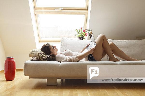 Entspannte Frau auf der Couch liegend mit Laptop