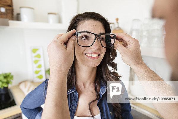 Mann setzt Frau auf überdimensionale Brille