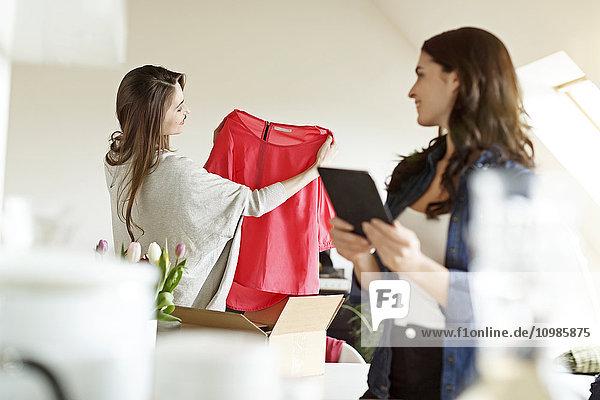 Zwei Frauen mit digitalem Tablett und Paket mit Kleidungsstück