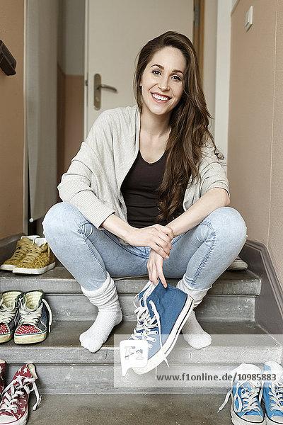 Lächelnde junge Frau sitzt auf der Treppe und hält Turnschuhe. Lächelnde junge Frau sitzt auf der Treppe und hält Turnschuhe.