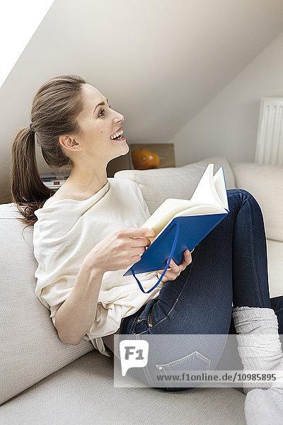 Glückliche Frau auf der Couch sitzend Lesebuch