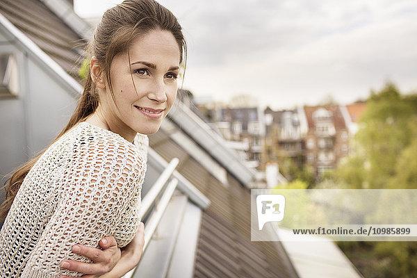 Lächelnde junge Frau auf dem Balkon stehend Lächelnde junge Frau auf dem Balkon stehend
