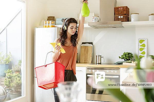 Junge Frau in der Küche putzen und Musik hören