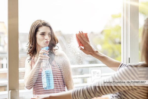 Zwei Frauen putzen gemeinsam das Fenster