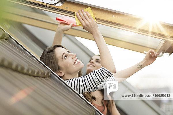 Lächelnde junge Frau putzt Dachfenster