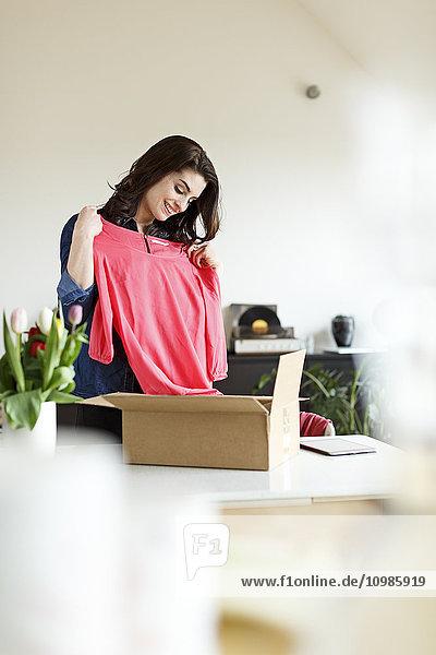 Lächelnde Frau zu Hause beim Auspacken des Pakets mit Kleidung