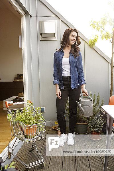 Lächelnde junge Frau mit Topfpflanze im Einkaufswagen auf dem Balkon