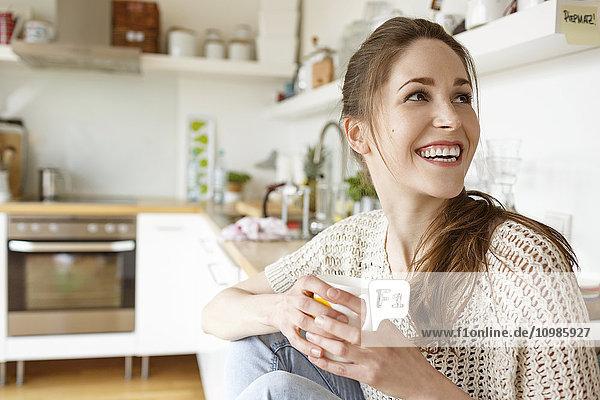 Fröhliche junge Frau mit einer Tasse Kaffee in der Küche