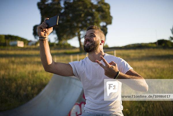 Mann nimmt Selfie und zeigt Siegeszeichen