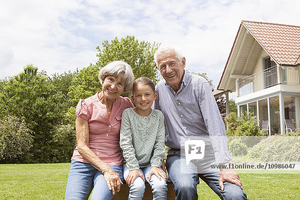 Portrait of happy grandparents with granddaughter in garden