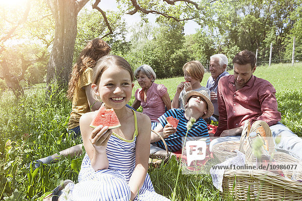 Mädchen mit Wassermelone beim Familienpicknick auf der Wiese