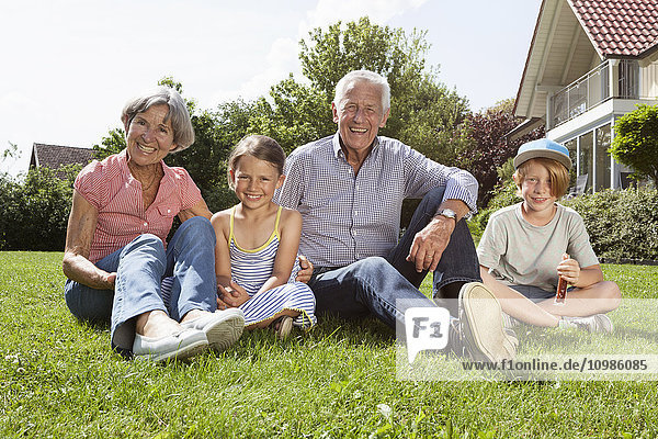 Portrait of happy gandparents with grandchildren in garden