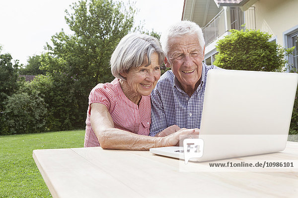Lächelndes Seniorenpaar mit Laptop im Garten