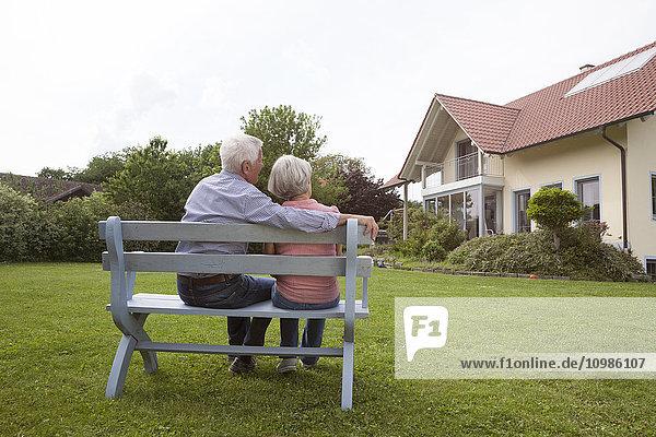Seniorenpaar auf Bank im Garten sitzend