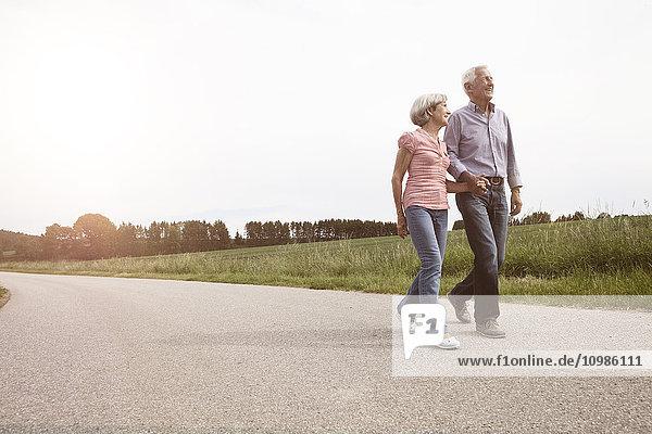 Lächelndes Seniorenpaar auf der Landstraße